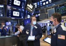 In this photo provided by the New York Stock Exchange, traders Gregory Rowe, center, and Robert Charmak, right, confer on the trading floor, Friday, May 7, 2021. Stocks are rallying to records on Wall Street Friday despite a stunningly disappointing report on the nation's job market, as investors see it helping to keep interest rates low. (Nicole Pereira/New York Stock Exchange via AP)