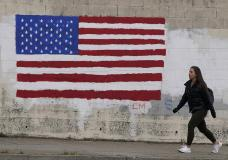 A pedestrian walks in front of an American flag painted on a wall during the coronavirus outbreak in San Francisco, Thursday, May 13, 2021. Counties in California are waiting for guidance from the state after the federal government on Thursday said that fully vaccinated people can quit face coverings and social distancing in most situations. California's Department of Public Health did not immediately respond to questions about whether it would adopt new guidance announced by the Centers for Disease Control and Prevention. (AP Photo/Jeff Chiu)