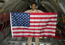 """In this Dec. 28, 2009 photo provided by Retired Air Force Lt. Col. Stephanie Davis, she holds a U.S. flag in the cargo area of a KC-135 airplane while flying over Pakistan/Afghanistan. For Davis, who grew up poor, the military was a path to the American dream, a realm where everyone would receive equal treatment. But many of her service colleagues, Davis says, saw her only as a Black woman. Or for the white resident colleagues who gave her the call sign of ABW – it was a joke, they insisted – an """"angry black woman,"""" a classic racist trope. (Courtesy Stephanie Davis via AP)"""