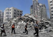 People inspect the the rubble of the Yazegi residential building that was destroyed by an Israeli airstrike, in Gaza City, Sunday, May 16, 2021. The 57-member Organization of Islamic Cooperation held an emergency virtual meeting Sunday over the situation in Gaza calling for an end to Israel's military attacks on the Gaza Strip. (AP Photo/Adel Hana)