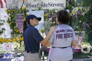 Miami Beach police chaplain Omy Llaneras, left, stands with a woman at a makeshift memorial near the Champlain Towers South condo building, where scores of victims remain missing more than a week after it partially collapsed, Saturday, July 3, 2021, in Surfside, Fla. (AP Photo/Lynne Sladky)