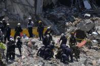 Search and rescue personnel work atop the rubble at the Champlain Towers South condo building, where scores of victims remain missing more than a week after it partially collapsed, Friday, July 2, 2021, in Surfside, Fla. (AP Photo/Mark Humphrey)