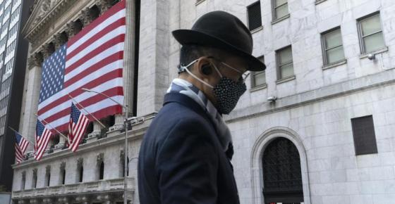 FILE - In this Nov. 16, 2020 file photo a man wearing a mask passes the New York Stock Exchange in New York. Stocks are opening higher on Wall Street following solid reports on economic growth and better-than-expected results from several major companies. The S&P 500 rose 0.5% in the early going Thursday, July 29, 2021. (AP Photo/Mark Lennihan, File)