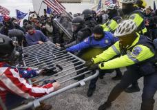 FILE - In this Jan. 6, 2021, file photo violent insurrectionists loyal to President Donald Trump hold on to a police barrier at the Capitol in Washington. The Senate has voted to award Medals of Honor to the Capitol Police and the Metropolitan Police Department for protecting Congress during the Jan. 6 insurrection, sending the legislation to President Joe Biden for his signature.  The bill passed by voice vote with no objections. The four medals will be displayed at Capitol Police headquarters, the Metropolitan Police Department, the U.S. Capitol and the Smithsonian Institution. Hundreds of officers from the two police departments responded to the attack as the mob of former President Donald Trump's supporters broke into the building and interrupted the certification of Biden's victory.  (AP Photo/John Minchillo, File)