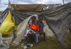 Earthquake-displaced people sit under blankets to shield themselves from the rain, the morning after Tropical Storm Grace swept over Les Cayes, Haiti, early Tuesday, Aug. 17, 2021, three days after a 7.2-magnitude earthquake. (AP Photo/Joseph Odelyn)