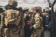 In this Aug. 22, 2021, photo provided by the U.S. Marines, U.S. service members provide assistance during an evacuation at Hamid Karzai International Airport in Kabul, Afghanistan. (Staff Sgt. Victor Mancilla/U.S. Marine Corps via AP)