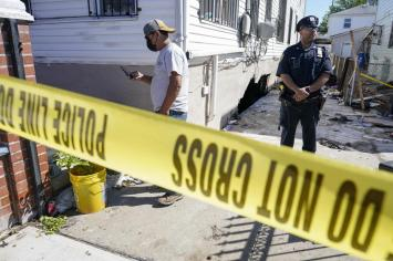A police officer stands guard as a man survey the damage to home where people died after their basement apartment flooded in the Jamaica neighborhood of the Queens borough of New York, Thursday, Sept. 2, 2021, in New York. The remnants of Hurricane Ida dumped historic rain over New York City, with several deaths linked to flooding in the region as basement apartments suddenly filled with water and freeways and boulevards turned into rivers, submerging cars.(AP Photo/Mary Altaffer)