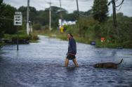 A resident wades through a flooded street after the remnants of Hurricane Ida passed through the area, Thursday, Sept. 2, 2021, in Narragansett, R.I. (AP Photo/David Goldman)