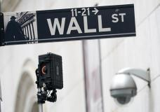 FILE - A Wall Street sign is seen next to surveillance equipment outside the New York Stock Exchange, Tuesday, Oct. 5, 2021, in New York. Stocks are off to a mostly lower start on Wall Street Thursday, Oct. 21, 2021 a day after the S&P 500 and the Dow Jones Industrials approached the record highs they set this summer. (AP Photo/Mary Altaffer)