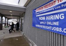 """FILE - In this Dec. 10, 2020, file photo, a """"Now Hiring"""" sign hangs on the front wall of a Harbor Freight Tools store in Manchester, N.H. When the U.S. government issues the September jobs report on Friday, Oct. 8, 2021, the spotlight will fall not only on how many people were hired last month. A second question will command attention, too: Are more people finally starting to look for work? (AP Photo/Charles Krupa, File)"""