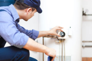 safety technician adjusting a water heater