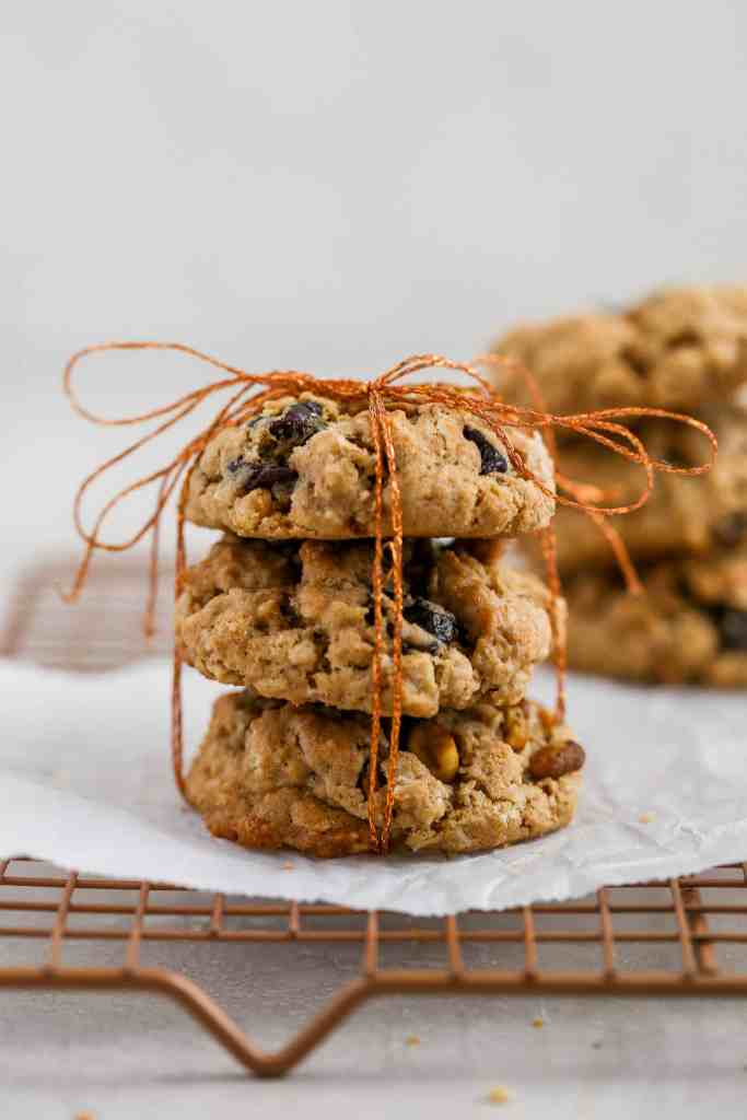 Cherry pistachio oatmeal cookies tied up with string displayed on a cookie rack.