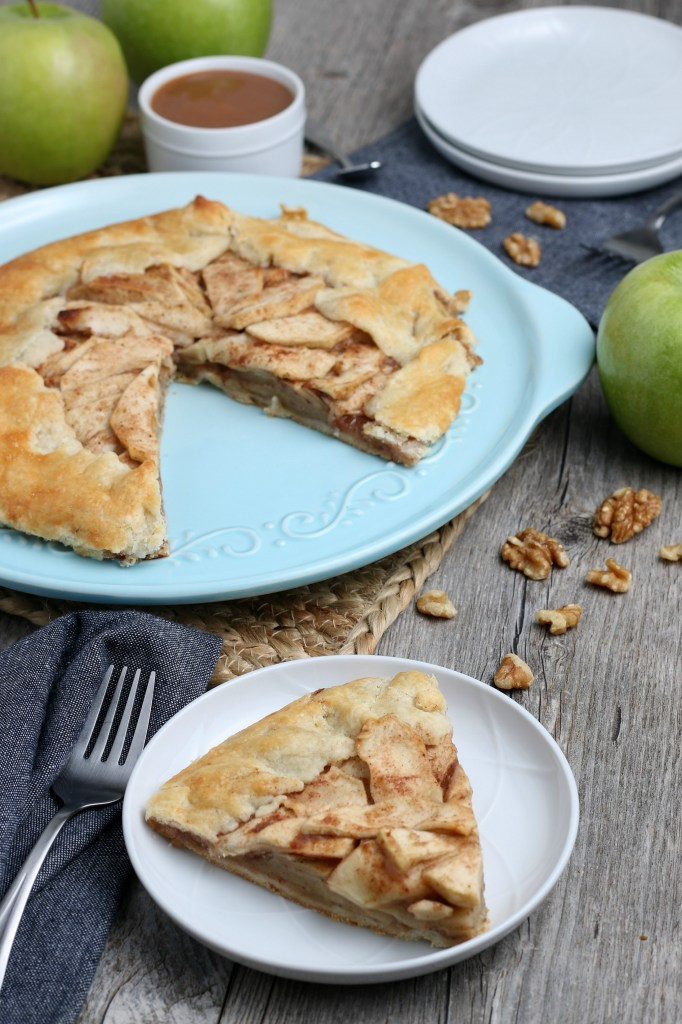 apple crostata with a slice on a while plate with a fork
