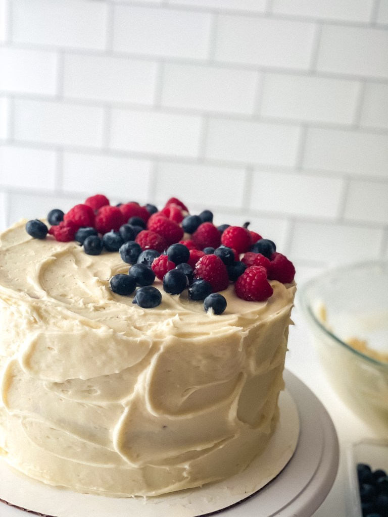 berry chantilly cake on a white cake stand with mixed berries piled on top