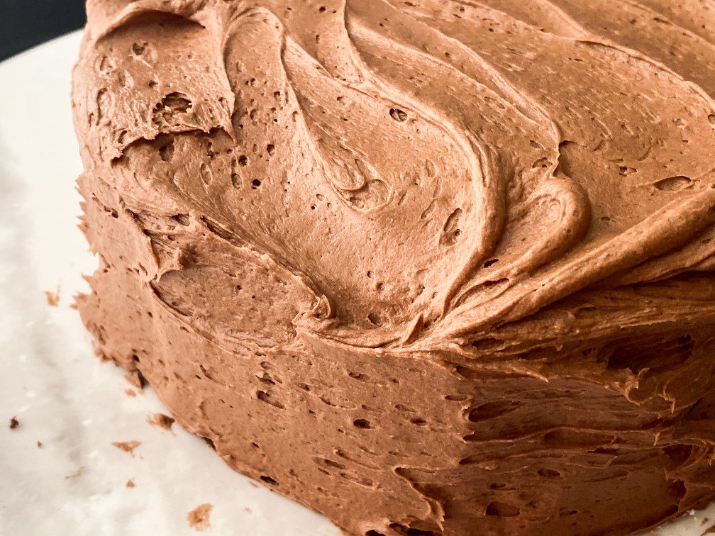 close up of chocolate frosting homemade and spread on a cake