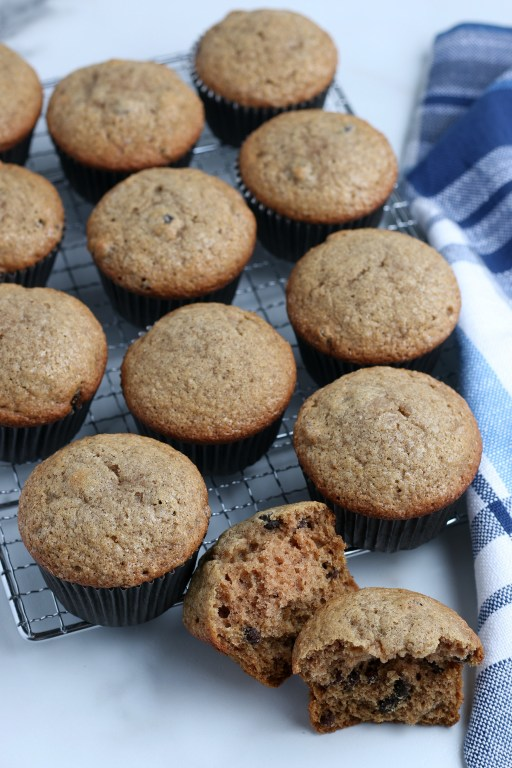 applesauce muffins sitting on a cooling rack with a blue towel