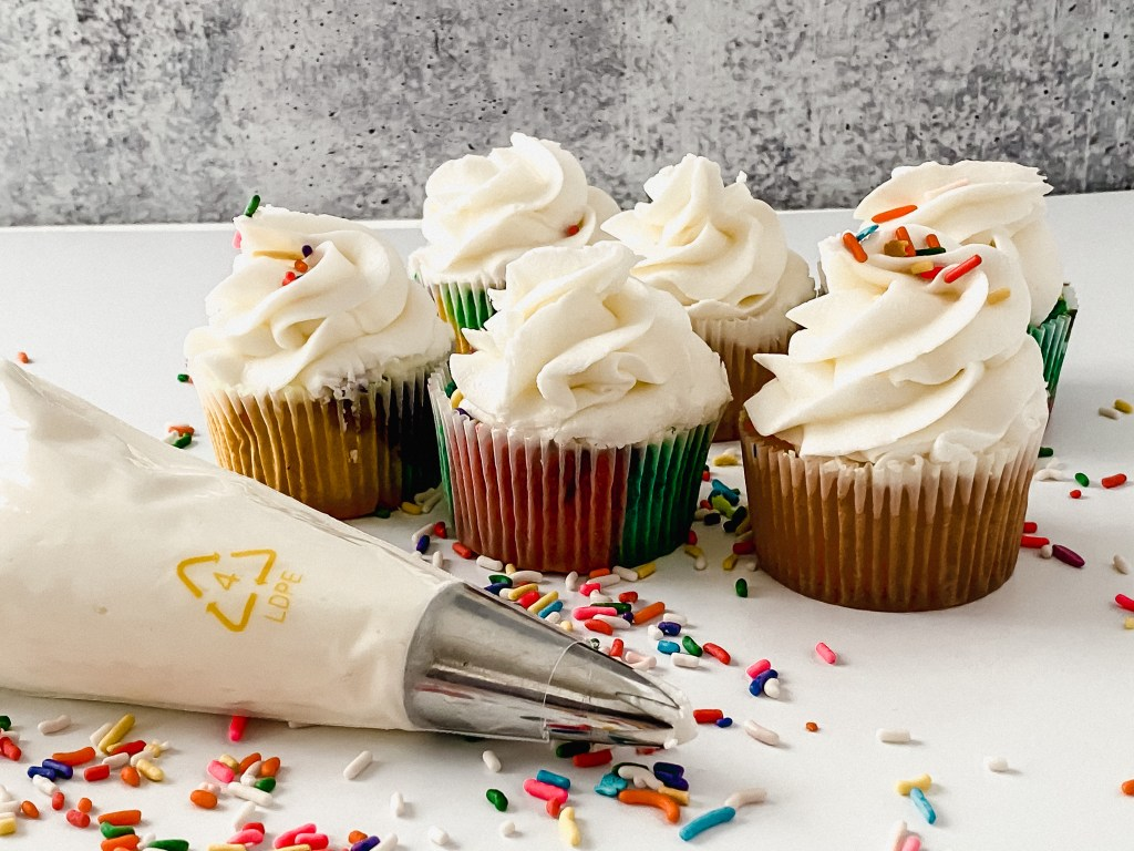 piping bag full of vanilla buttercream frosting with cupcakes