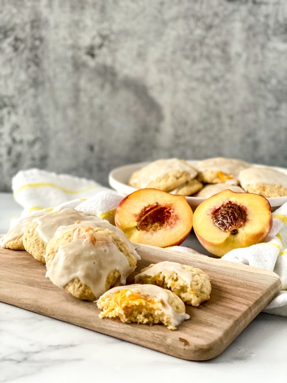 peach cobbler cookies with peaches, tea towel, and wooden board