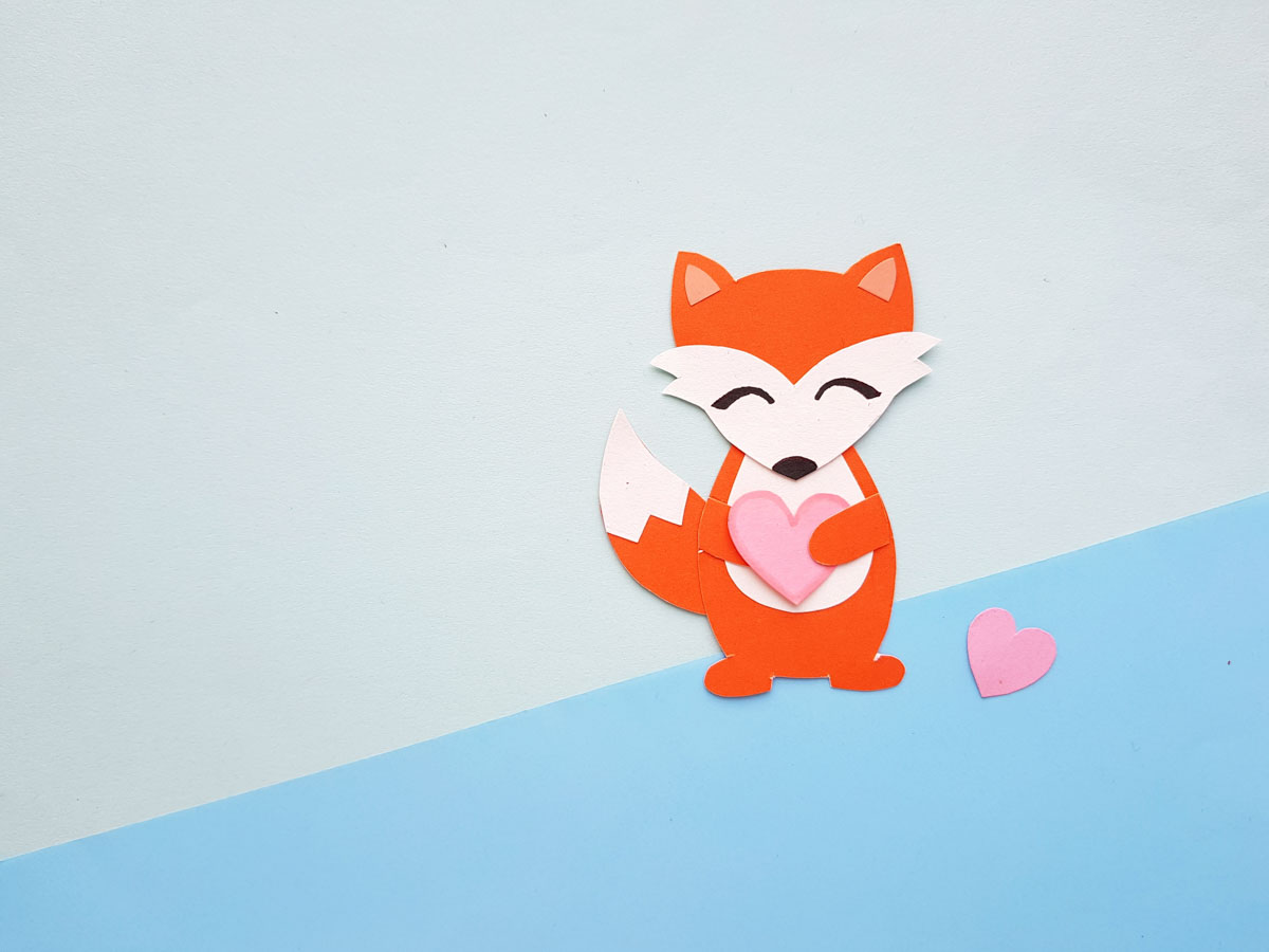 Red fox papercraft on blue paper holding a pink heart