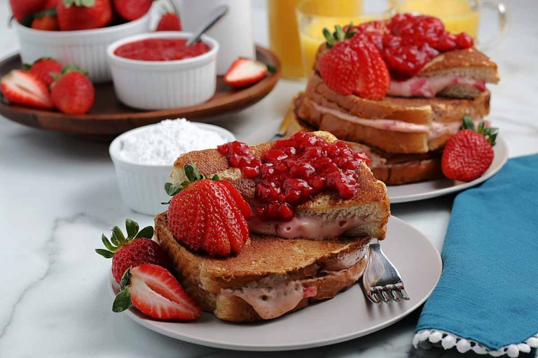 strawberry stuffed French toast on a white platter with fork.