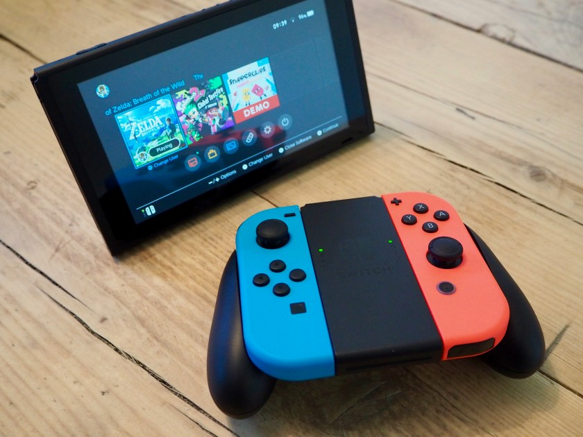 Nintendo Switch with detached Joy-Con controllers in the controller grip accessory