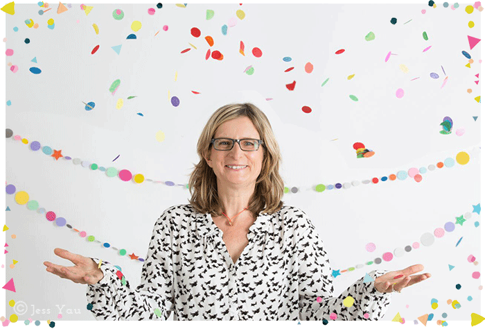 Clare Burgess headshot with confetti. Wide shot