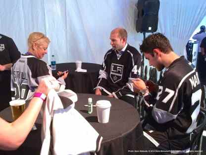 Defensemen Robyn Regehr (center) and Alec Martinez (right) greet a fan