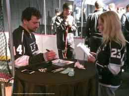 Right wing Justin Williams signs an autograph for a fan