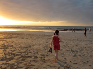girl walking on the beach at sunset