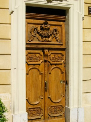 Ornately carved door with varnish and stone surrounds in provence