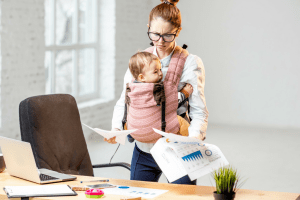 Woman standing at desk while wearing baby - What Corporate Managers & Stay-At-Home Moms Have In Common