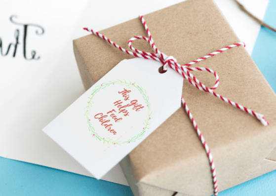 "Gift tag that reads, ""This Gift Helps Feed Children"" - 5 Ways To Give Eco-Friendly Holiday Gifts With Printable Card & Gift Tags"
