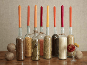 Use clear or colored bottles and fill with corn kernels and spices. Top each with a candle. Image courtesy of http://blog.2shopper.com/2013/11/13/13-creative-diy-thanksgiving-centerpieces/