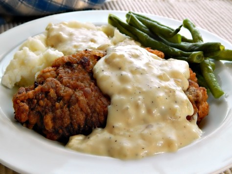 Chicken Fried Steak with Country Gravy. (the little lumpies are onion,)