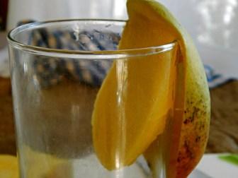 Slide mango down the lip of a glass