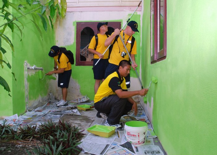 US and Malaysian Sailors paint a house as part of a community service project.