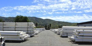 White Pipes StackedTightly In Front of Mountainous Landscape and Blue Skies With Clouds