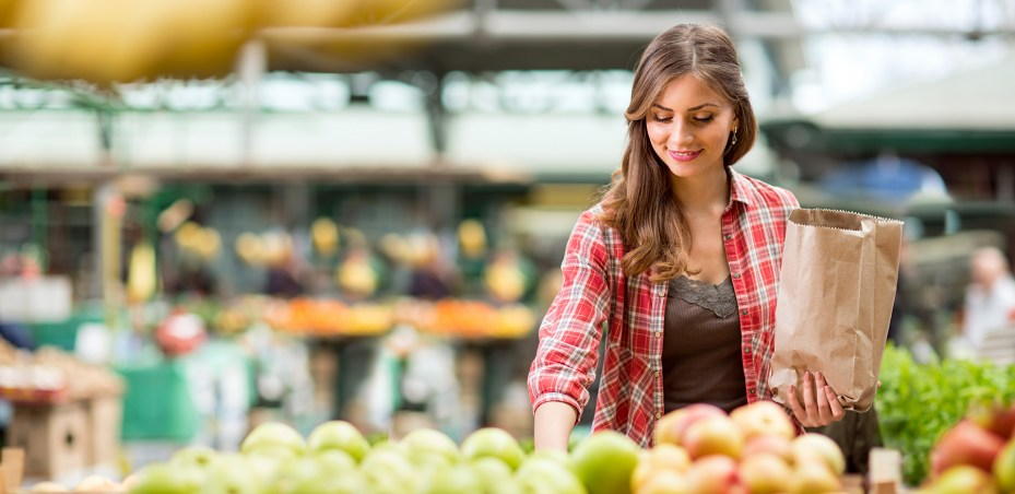Woman With Brown Hair and Plaid Shirt at a Grocery Store Picking Out Apples