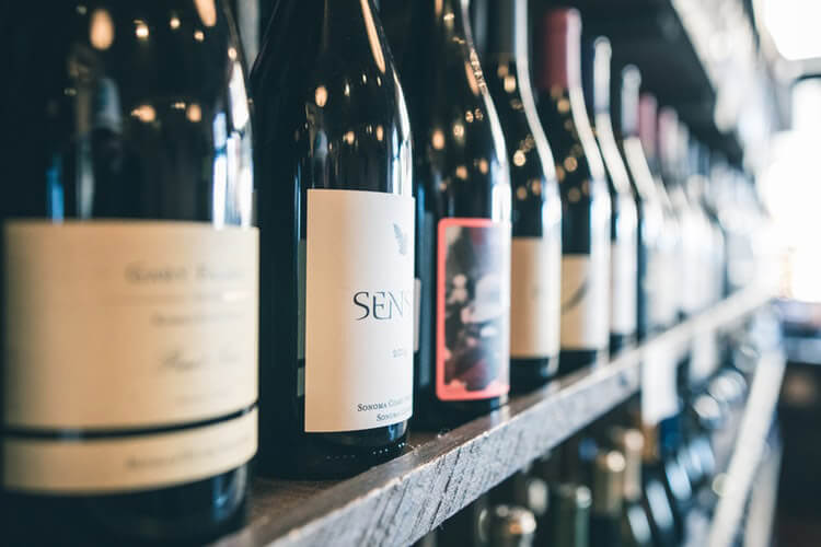 Napa Valley wine bottles on a shelf.