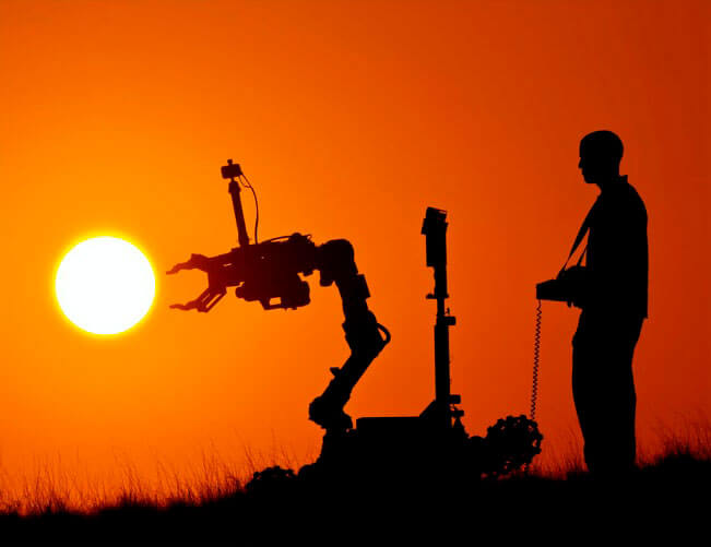 Man remote controlling robot at sunset