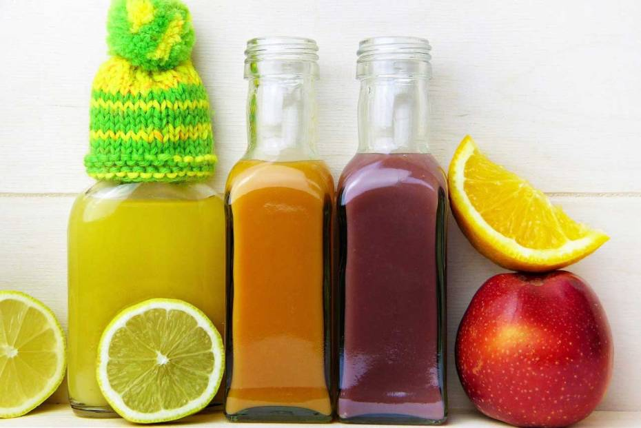 Bottles of lemon, orange, and apple juice with a knitted beanie.
