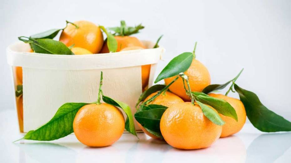 A small box of tangerines with leaves attached.
