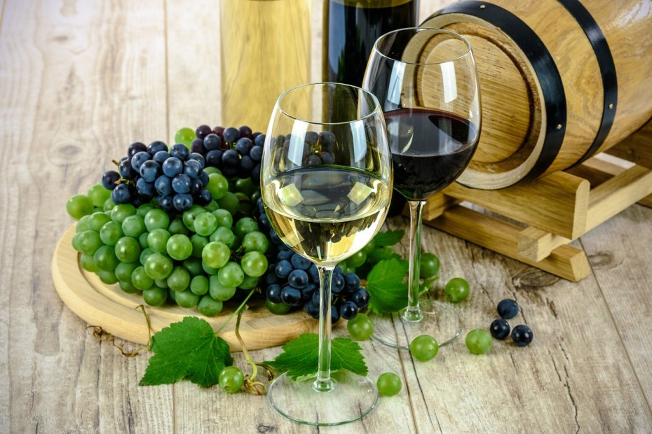 Green and purple grapes next to glasses of red and white wine.
