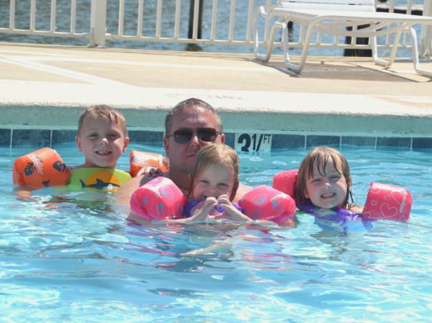 Triplets and dad in pool