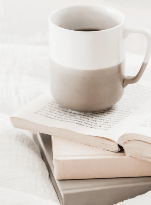Coffee mug on top of open books