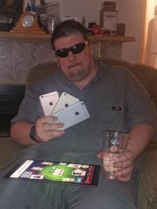Picture of Fry with iPad in lap, holding 3 iPhones as if they were playing cards