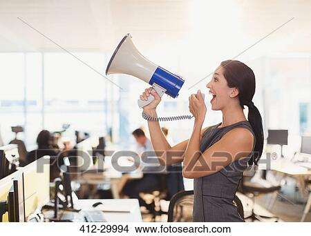 Exuberant businesswoman using megaphone in office Picture | 412-29994 | Fotosearch