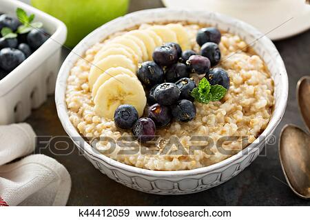 Steel cut oatmeal porridge with banana and blueberry Stock Photo | k44412059 | Fotosearch