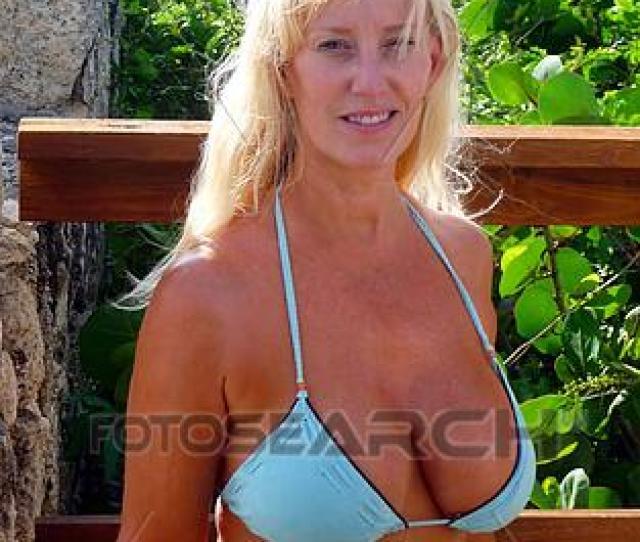 Blonde Adult Girl Standing By Rock Wall In Bikini On A Tropical Island