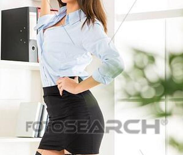 Pretty Young Business Woman In A Short Skirt Standing In Front Of Shelves With Binders And With A Smile Looking At The Camera